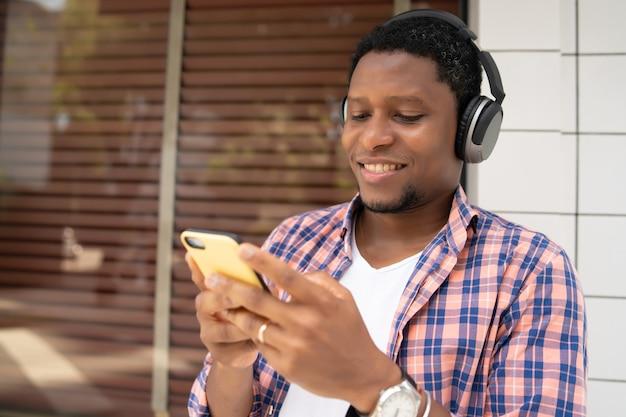 Afro-amerikaanse man die zijn mobiele telefoon gebruikt terwijl hij buiten op straat staat