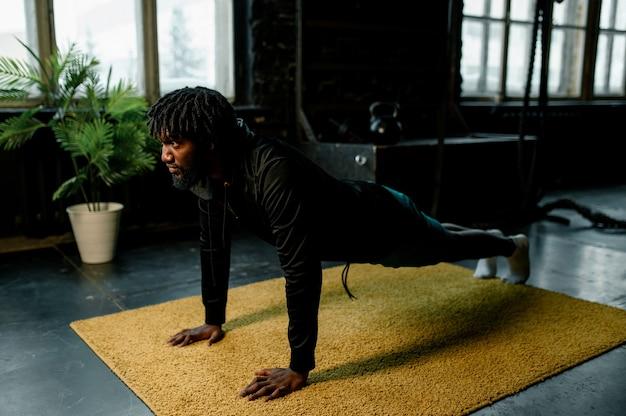 Afro-amerikaanse man doet push-ups in moderne sportschool met grote ramen