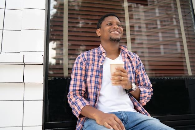Afro-amerikaanse man drinken van een kopje koffie terwijl u buiten de coffeeshop zit. stedelijk concept.