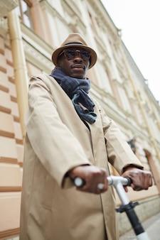 Afro-amerikaanse man elektrische scooter rijden