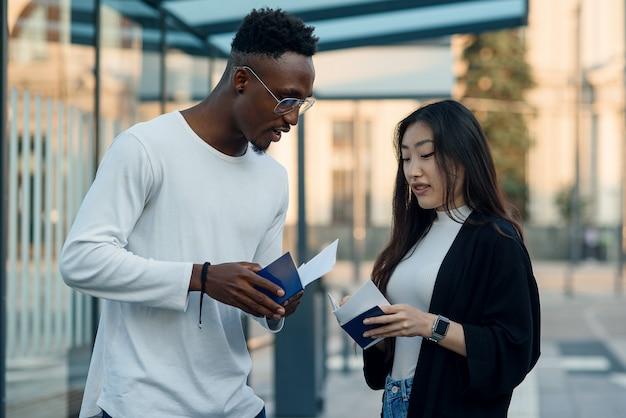 Afro-amerikaanse man en aziatische vrouw met paspoorten en praten bij bushalte.