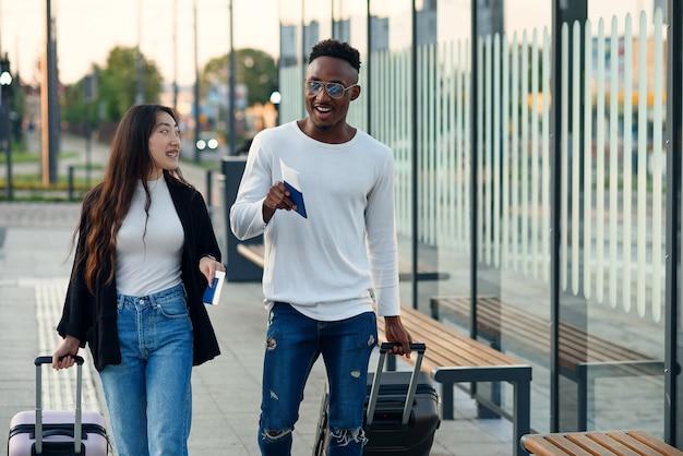 Afro-amerikaanse man en aziatische vrouw met paspoorten houden koffers en praten bij bushalte.