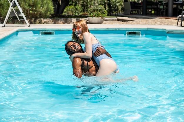 Afro-amerikaanse man en blanke vrouw spelen in een pool.