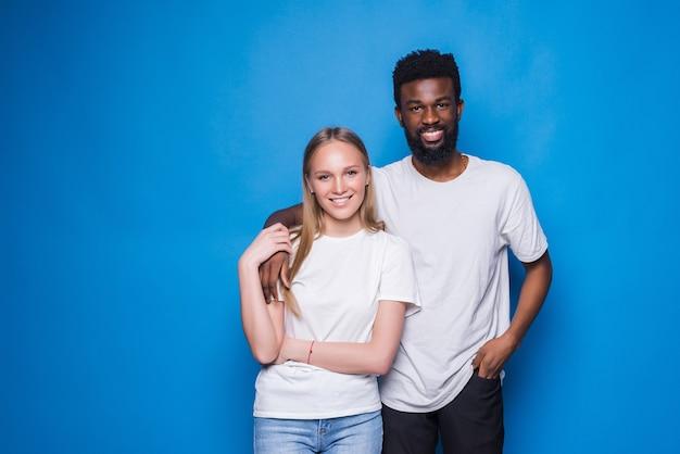 Afro-amerikaanse man en mooie blanke vrouw divers paar verliefd, steun en zorg, geïsoleerd op blauwe muur
