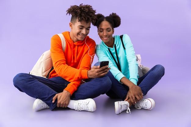 Afro-amerikaanse man en vrouw dragen rugzakken met behulp van smartphone en oortelefoons zittend op de vloer met gekruiste benen, geïsoleerd over violette muur