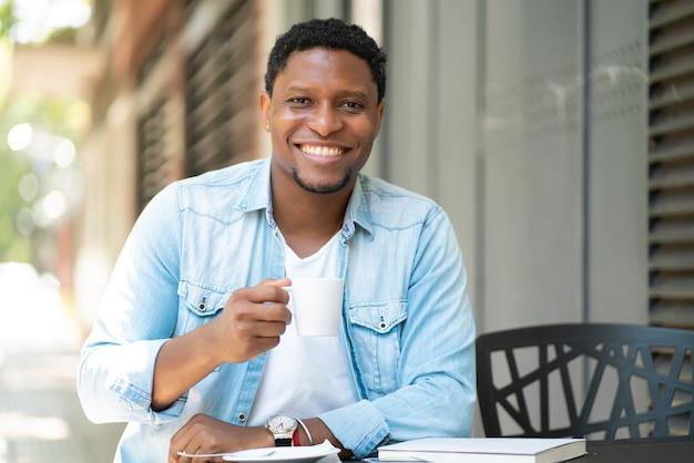 Afro-amerikaanse man genieten van en drinken van een kopje koffie zittend in de coffeeshop buitenshuis