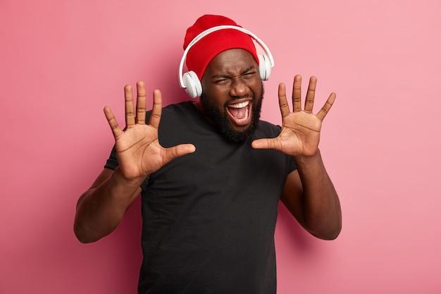 Afro-amerikaanse man houdt de handpalmen naar voren, opent zijn mond wijd, gekleed in een rode hoed en een zwart t-shirt, roept uit van vreugde, geniet van muziek in koptelefoons