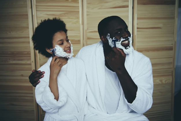 Afro-amerikaanse man in badjas leert zoon.