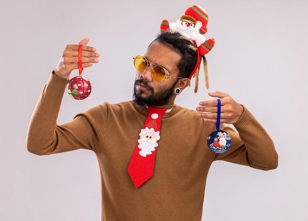 Afro-amerikaanse man in bruine trui en kerstman rand op hoofd met grappige rode stropdas met kerstballen kijken verward proberen een keuze te maken staande over witte muur