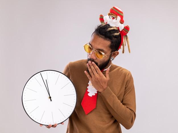 Afro-amerikaanse man in bruine trui en santa rand op hoofd met grappige rode stropdas bedrijf klok kijken verbaasd staande op witte achtergrond