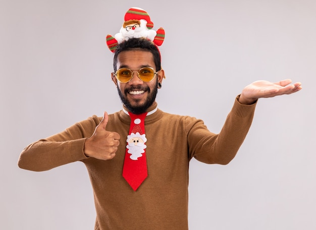 Afro-amerikaanse man in bruine trui en santa rand op hoofd met grappige rode stropdas duimen opdagen presenteren met arm glimlachend vrolijk staande op witte achtergrond