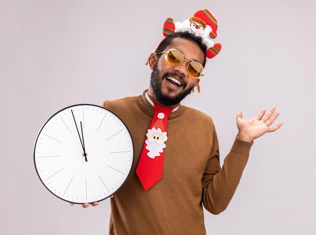 Afro-amerikaanse man in bruine trui en santa rand op hoofd met grappige rode stropdas houden klok kijken camera glimlachend vrolijk met opgeheven arm staande op witte achtergrond