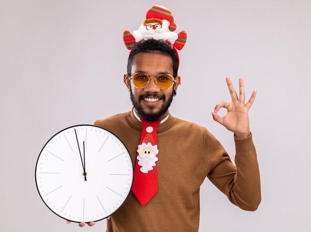 Afro-amerikaanse man in bruine trui en santa rand op hoofd met grappige rode stropdas houden klok kijken camera glimlachend vrolijk tonen ok teken staande op witte achtergrond