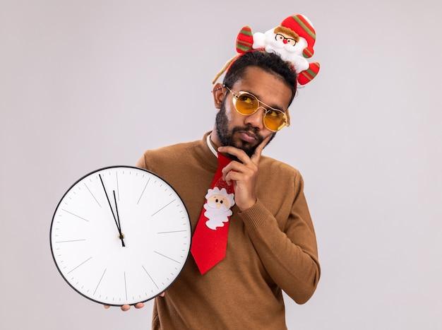Afro-amerikaanse man in bruine trui en santa rand op hoofd met grappige rode stropdas houden klok kijken verbaasd staande op witte achtergrond