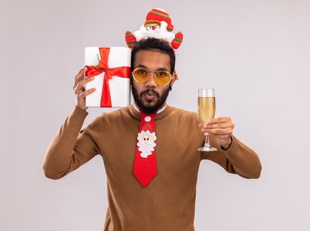 Afro-amerikaanse man in bruine trui en santa rand op hoofd met grappige rode stropdas met een cadeau en glas champagne kijken camera verrast staande op witte achtergrond