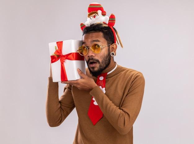 Afro-amerikaanse man in bruine trui en santa rand op hoofd met grappige rode stropdas met een cadeautje kijken camera verrast staande op witte achtergrond