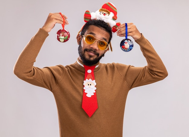 Afro-amerikaanse man in bruine trui en santa rand op hoofd met grappige rode stropdas met kerstballen met glimlach op gezicht staande over witte muur
