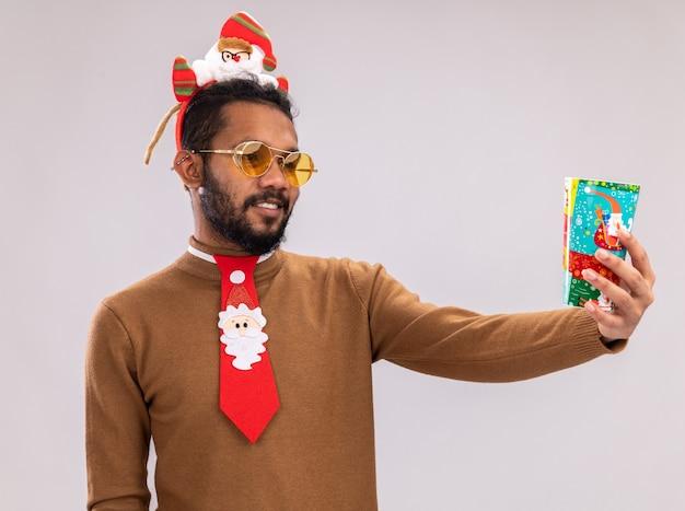 Afro-amerikaanse man in bruine trui en santa rand op hoofd met grappige rode stropdas met kleurrijke papieren beker kijken met glimlach op gezicht staande op witte achtergrond