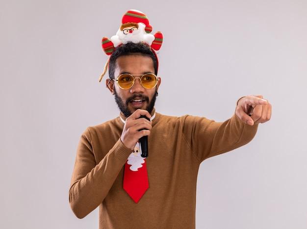 Afro-amerikaanse man in bruine trui en santa rand op hoofd met grappige rode stropdas met microfoon wijzend met wijsvinger naar de zijkant staande op witte achtergrond