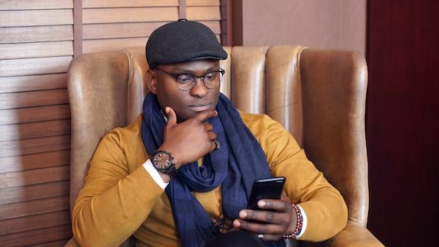 Afro-amerikaanse man in een gele jas en pet wacht op zijn vriend in de hal van het restaurant, zittend in een stoel, tijd doorbrengen met het kijken naar internet op een smartphone