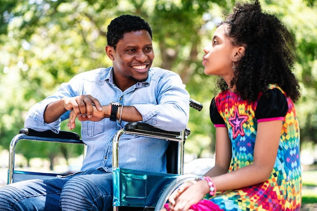 Afro-amerikaanse man in een rolstoel die geniet van en plezier heeft met haar dochter in het park.
