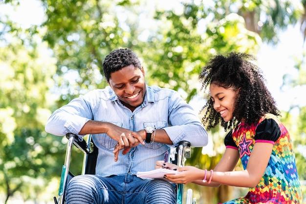 Afro-amerikaanse man in een rolstoel genieten van en plezier maken met haar dochter in het park