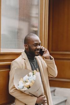 Afro-amerikaanse man in een stad. guy bedrijf boeket bloemen. mannetje in een bruine vacht.