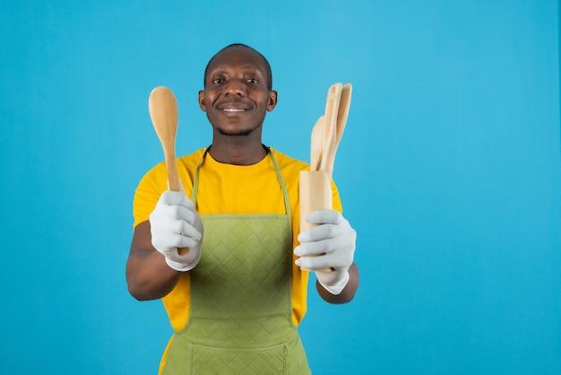 Afro-amerikaanse man in groene schort met houten keukengereedschap op blauwe muur