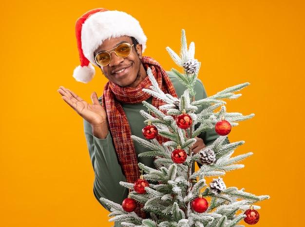 Afro-amerikaanse man in kerstmuts en sjaal om de nek blij en vrolijk lachend staande naast een kerstboom over oranje muur