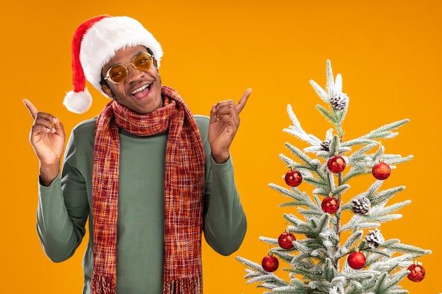 Afro-amerikaanse man in kerstmuts en sjaal om de nek glimlachend vrolijk naast een kerstboom over oranje muur