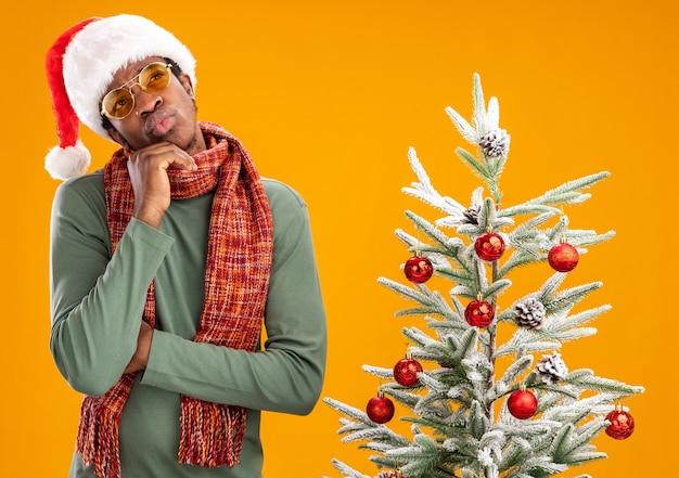 Afro-amerikaanse man in kerstmuts en sjaal om de nek kijken verbaasd staande naast een kerstboom op oranje achtergrond