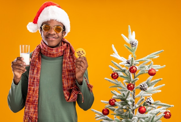 Afro-amerikaanse man in kerstmuts en sjaal om de nek met glas melk en cookie glimlachend staande naast een kerstboom op oranje achtergrond