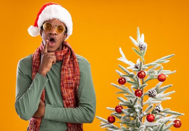 Afro-amerikaanse man in kerstmuts en sjaal om de nek verrast staande naast een kerstboom over oranje muur