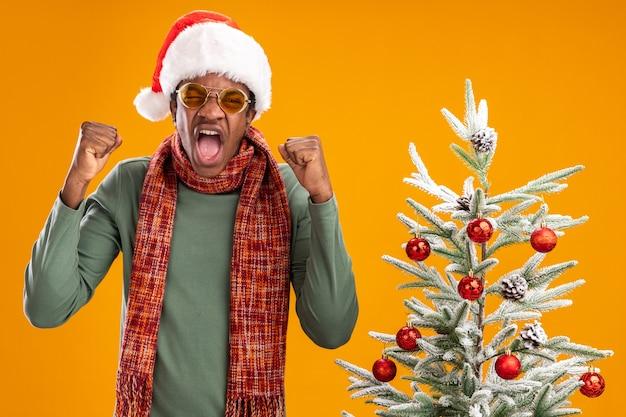 Afro-amerikaanse man in kerstmuts en sjaal om nek balde vuisten boos gek gekke staande naast een kerstboom op oranje achtergrond