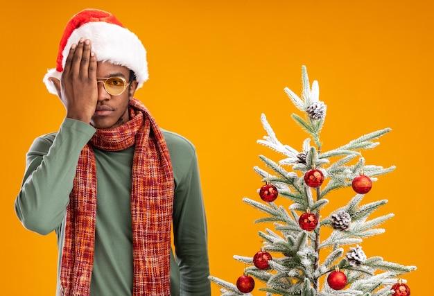 Afro-amerikaanse man in kerstmuts en sjaal om nek camera kijken met ernstig gezicht voor één oog met een hand die naast een kerstboom staat op oranje achtergrond
