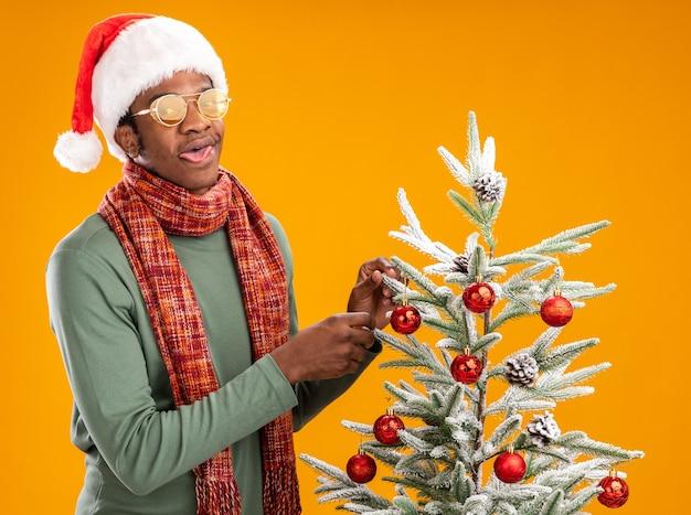 Afro-amerikaanse man in kerstmuts en sjaal om nek hangende kerstballen aan een kerstboom, gelukkig en positief over oranje achtergrond