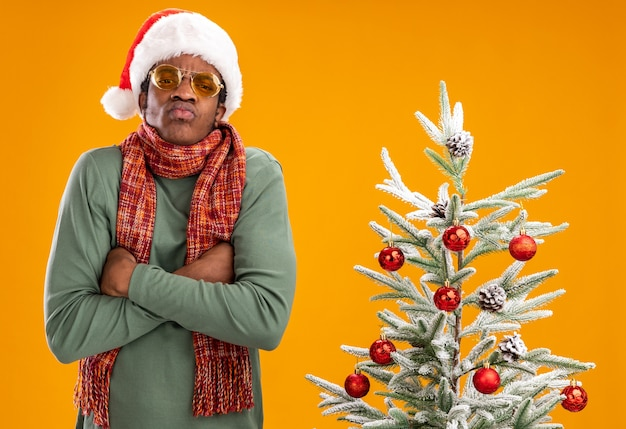 Afro-amerikaanse man in kerstmuts en sjaal om nek kijken camera ontevreden met gekruiste armen staande naast een kerstboom op oranje achtergrond