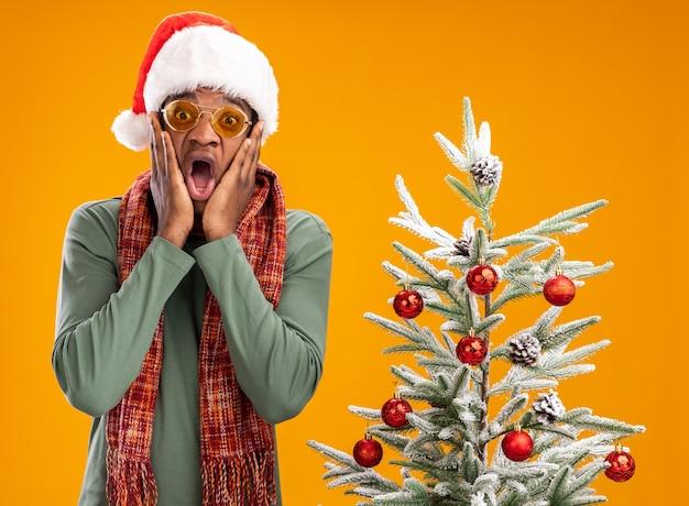 Afro-amerikaanse man in kerstmuts en sjaal om nek verbaasd en verrast naast een kerstboom over oranje muur