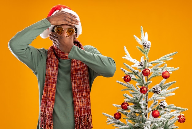 Afro-amerikaanse man in kerstmuts en sjaal rond de nek camera kijken met hand op zijn hoofd die mond bedekt met andere hand staande naast een kerstboom op oranje achtergrond