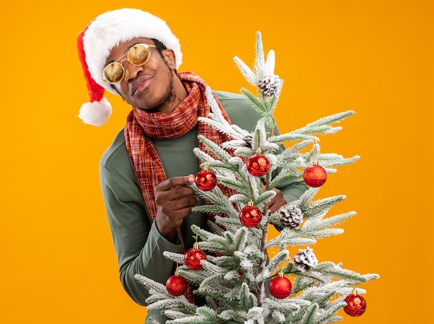 Afro-amerikaanse man in kerstmuts en sjaal rond de nek met een glimlach op het gezicht naast een kerstboom over oranje muur