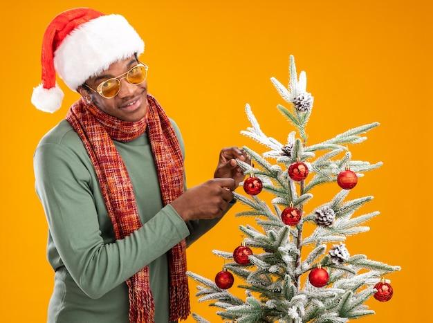 Afro-amerikaanse man in kerstmuts en sjaal rond de nek opknoping kerstballen op een kerstboom blij en positief staande over oranje muur
