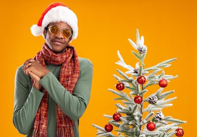 Afro-amerikaanse man in kerstmuts en sjaal rond nek kijken camera blij en positief glimlachend hand in hand samen naast een kerstboom staan op oranje achtergrond