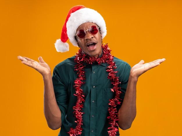 Afro-amerikaanse man in kerstmuts met slinger bril dragen verward schouders ophalen staande over oranje muur