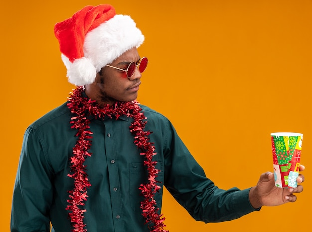 Afro-amerikaanse man in kerstmuts met slinger die zonnebril draagt ?? die kleurrijke papieren beker houdt die ernaar kijkt met een ernstig gezicht dat zich over oranje muur bevindt