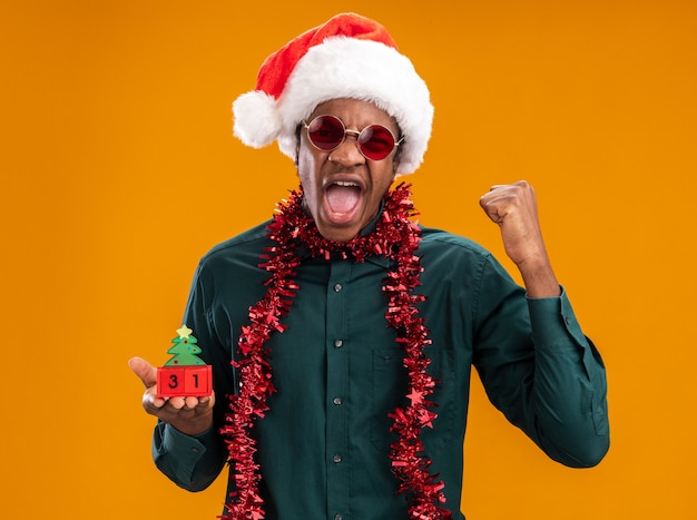 Afro-amerikaanse man in kerstmuts met slinger die zonnebril draagt ?? die stuk speelgoed kubussen met nieuwjaarsdatum houdt die met agressieve uitdrukking schreeuwen die zich over oranje muur bevindt