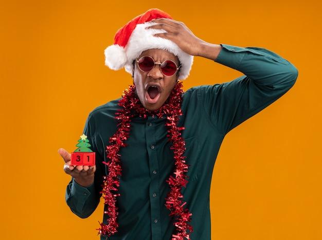 Afro-amerikaanse man in kerstmuts met slinger die zonnebril draagt ?? die stuk speelgoed kubussen met nieuwjaarsdatum houdt met boos gezicht met agressieve uitdrukking die zich over oranje muur bevindt