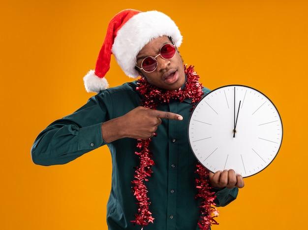 Afro-amerikaanse man in kerstmuts met slinger dragen van een zonnebril met klok wijzend met wijsvinger op het staande over oranje achtergrond