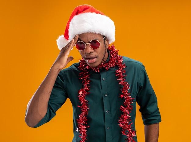 Afro-amerikaanse man in kerstmuts met slinger dragen van een zonnebril opzij kijken verward met de hand op zijn hoofd staande over oranje muur