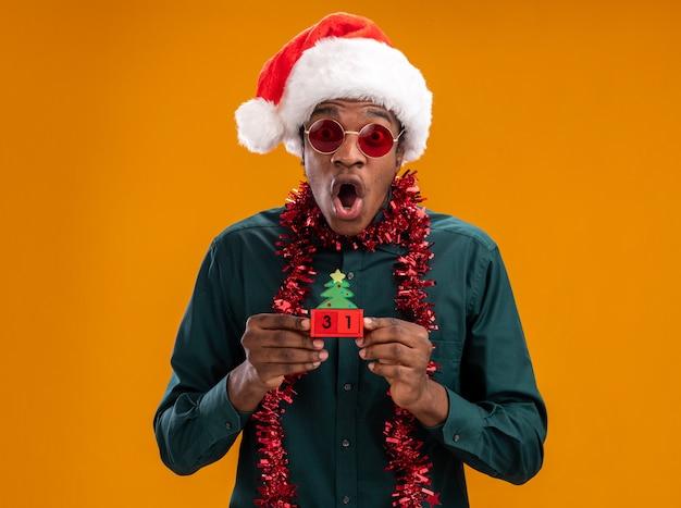 Afro-amerikaanse man in kerstmuts met slinger dragen van een zonnebril speelgoed blokjes met nieuwjaar datum kijken camera verbaasd en geschokt staande over oranje achtergrond