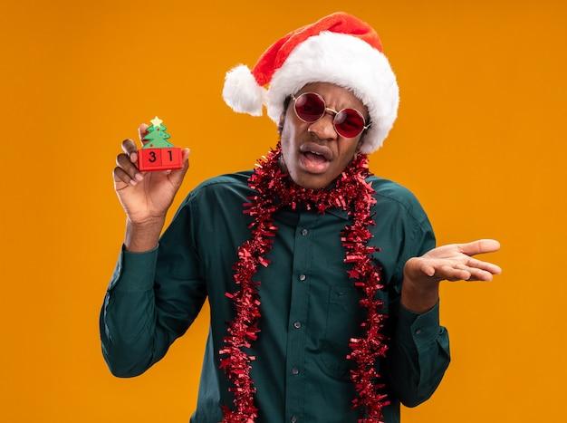 Afro-amerikaanse man in kerstmuts met slinger dragen van een zonnebril speelgoed kubussen met nieuwjaar datum kijken camera verward met arm uit staande over oranje achtergrond kijken